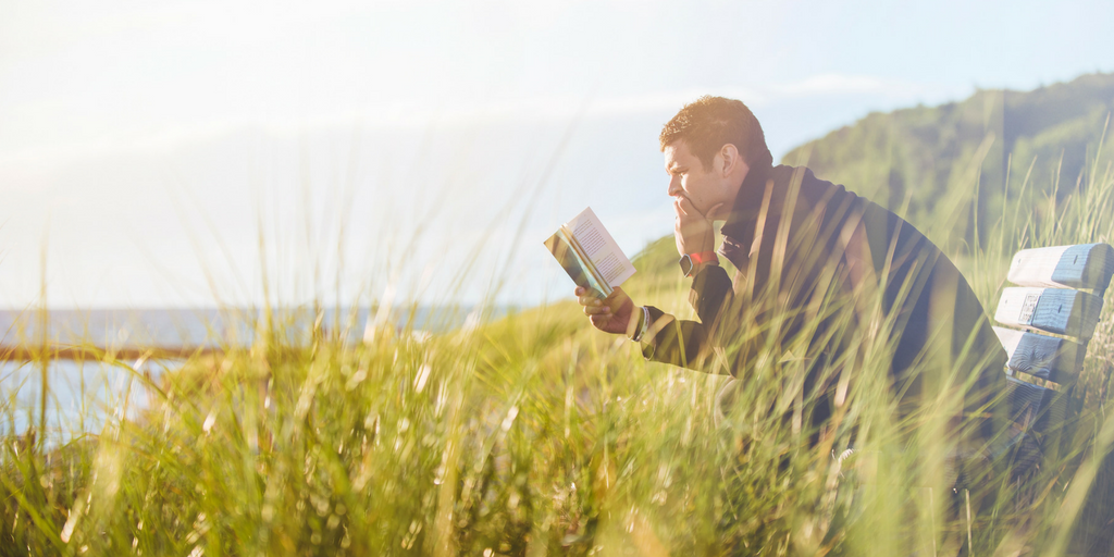 guy reading book.png